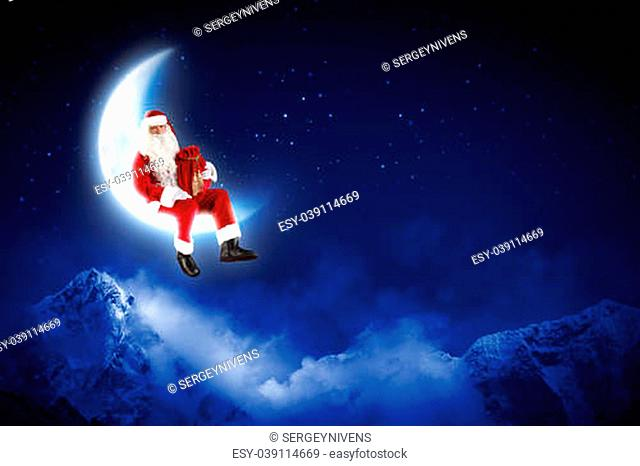 Photo of Santa Claus sitting on shiny moon above winter forest