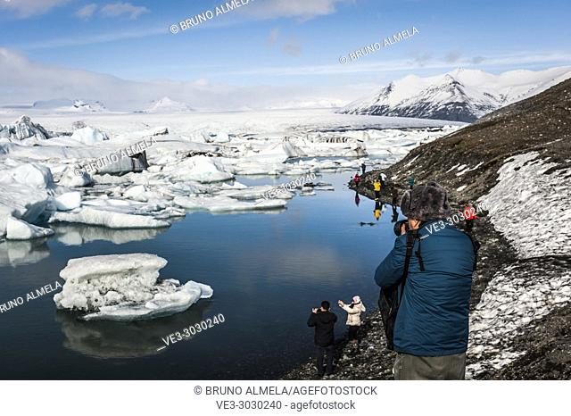 Tourists taking pictures to icebergs in Jökulsárlón Glacier Lagoon, Breidamerkurjökull Glacier (region of Austurland, Iceland)