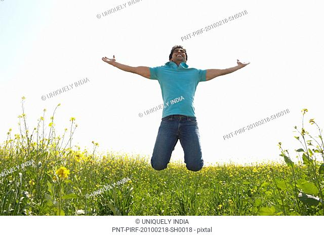 Man jumping with his arm outstretched in an oilseed rape field