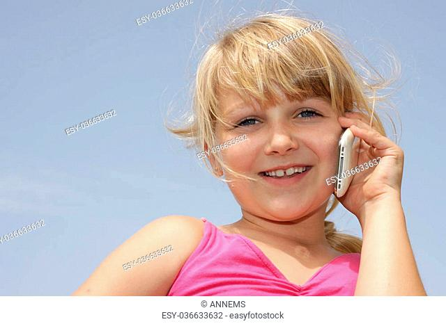 Horizontal photo of cute young girl talking on her mobile, Positive feeling. Space for text