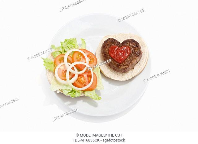 A heart shaped beef burger on a bun, with tomato sauce and a side salad
