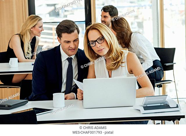 Businessman and businesswoman working together at office desk