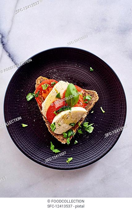 A slice of bread topped with tomatoes, mozzarella and basil (seen from above)