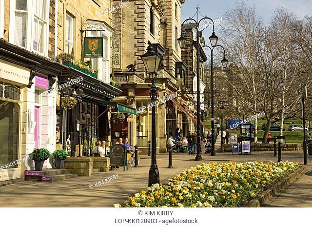 England, North Yorkshire, Harrogate, People sitting outside cafes on Montpellier Parade enjoying the spring sunshine