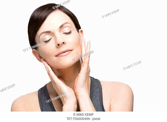 Woman with eyes closed on white background