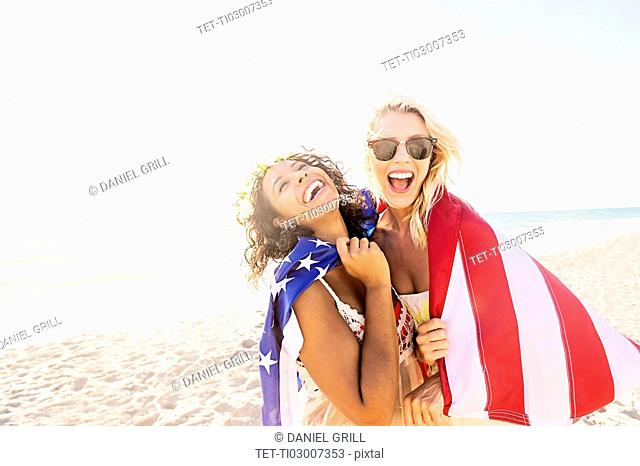 Female friends on beach with American flag