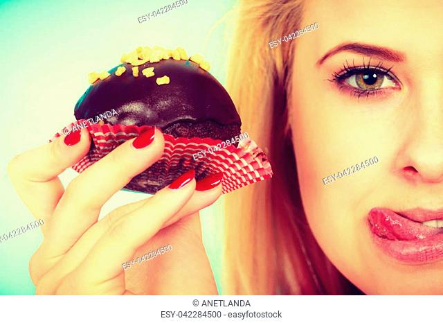 Diet, sweets, food concept. Cute blonde attractive woman about to eat delicious chocolate cupcake, sticking her tongue out