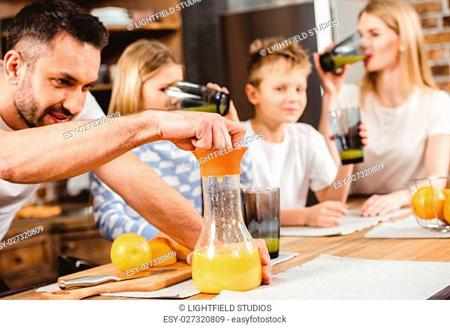 Young man makes orange juice for his family for breakfast