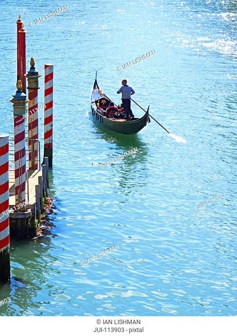 Gondolier paddling tourists in gondola on sunny Grand Canal, Venice, Italy