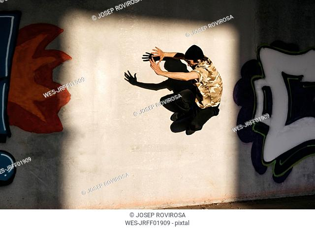 Man doing breakdance in urban concrete building, jumping against wall with graffitis