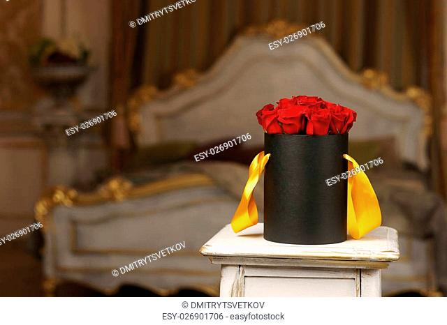 Red roses in black box. Expensive present in luxury interior of bedroom