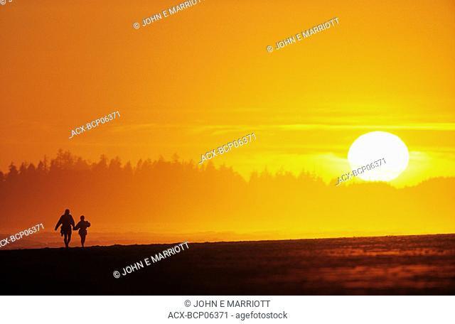 Couple walking on Long Beach at sunset, Pacific Rim National Park, British Columbia, Canada