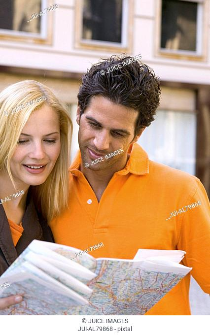 Couple reading map in urban area