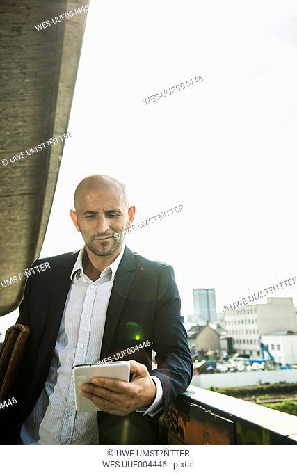 Confident businessman on bridge using digital tablet
