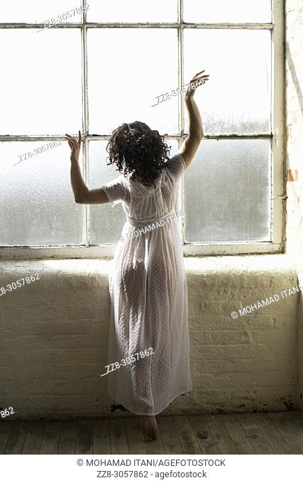 Rear view of a young woman wearing a white gown dancing by the window