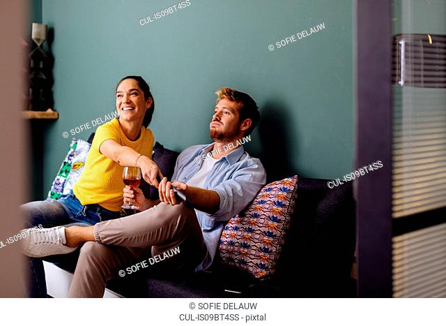 Young woman taking tv remote control from man on couch