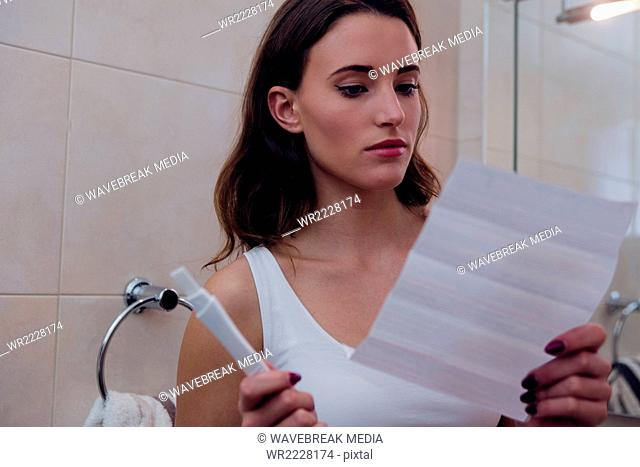Beautiful brunette reading pregnancy test instructions