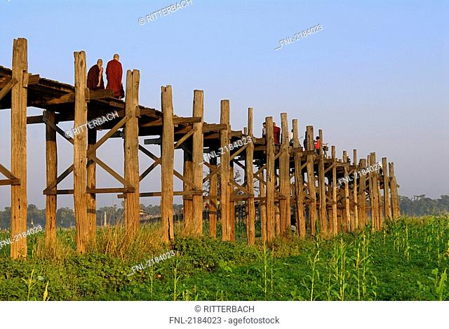 Low angle view of monks on footbridge, U Bein Bridge, Amarapura, Mandalay, Myanmar