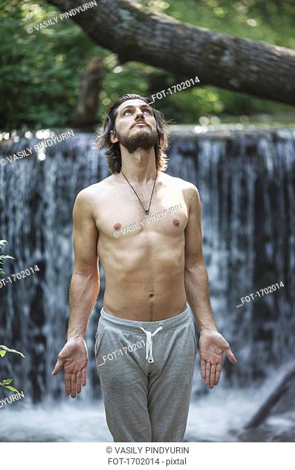 Shirtless young man looking up while standing against waterfall at forest