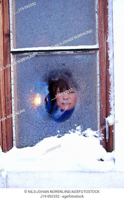 Winter, strong cold. Icy windows. 11 years old boy and a lantern