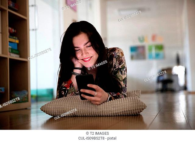 Teenage girl lying on cushion on floor reading text message