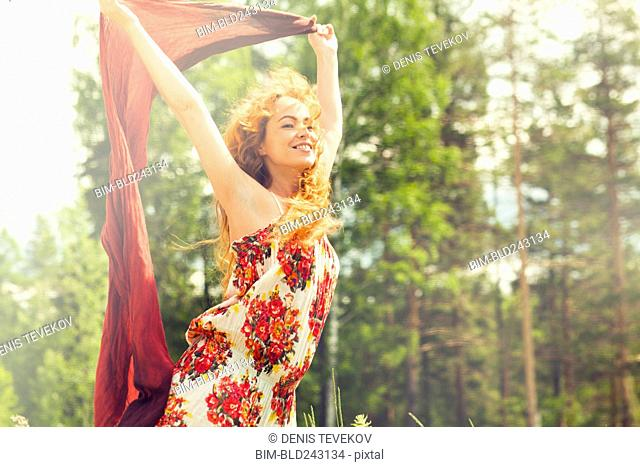 Caucasian woman holding scarf in wind