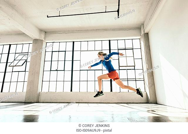 Side view of young woman in gym doing powerful mid air running stance