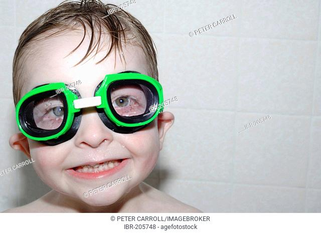 Young boy wearing swim goggles in the bath