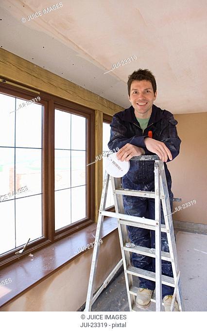 Smiling man holding smoke detector on ladder