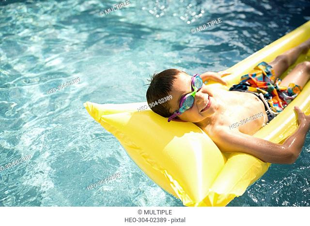 Portrait smiling boy wearing goggles laying on pool raft in sunny swimming pool