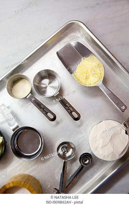Overhead view of raw pastry baking ingredients with scoop and measuring spoons