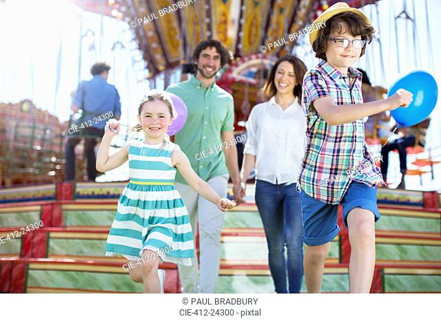 Children running in front of carousel, parents following them