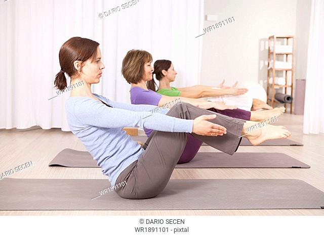 Three women doing Pilates exercises in gym