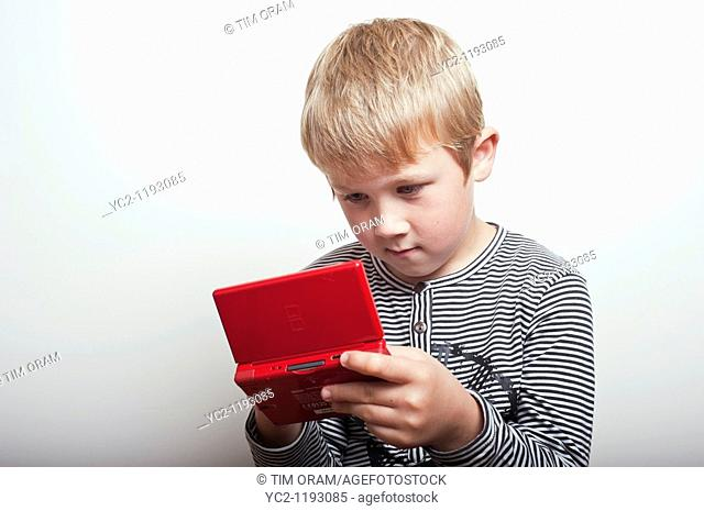 6 year old boy playing with a Nintendo DS handheld games console in the studio