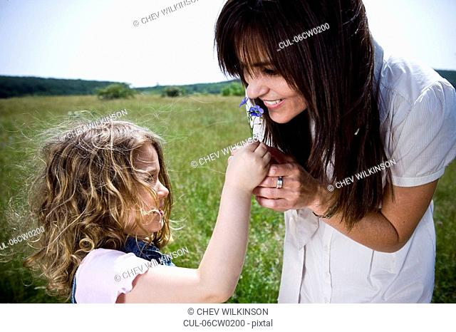 Woman smelling flower with daughter