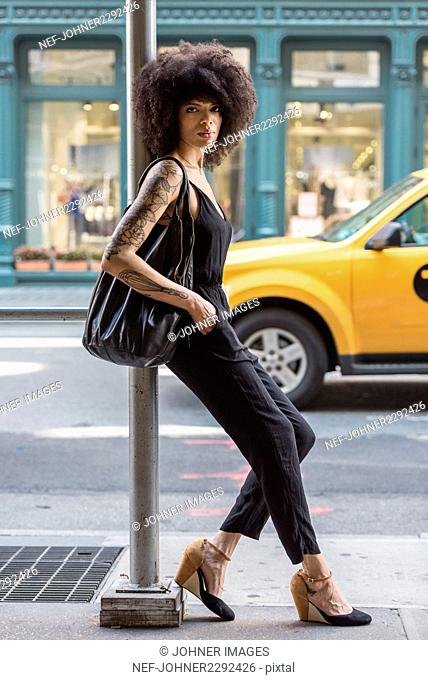 Fashionable woman leaning on pole in city