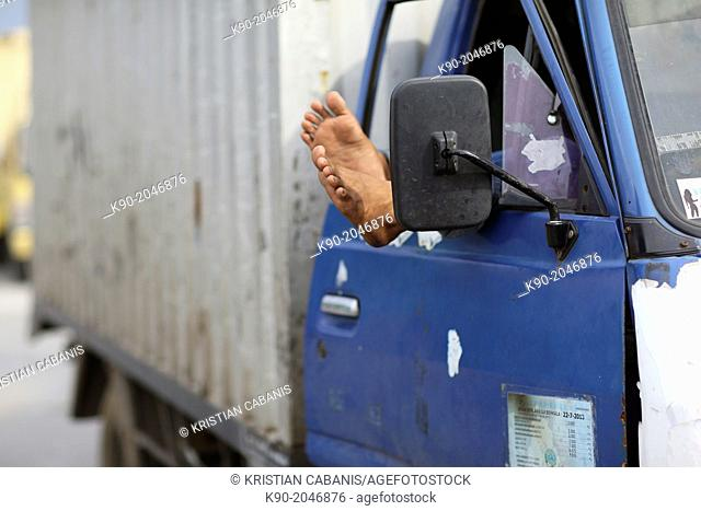 Feet hanging out of the window of a truck, Jakarta, Java, Indonesia, Southeast Asia