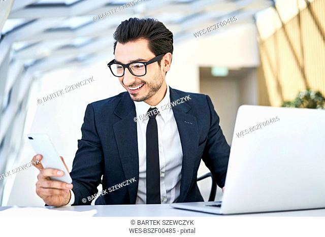 Smiling businessman looking at cell phone at desk in modern office
