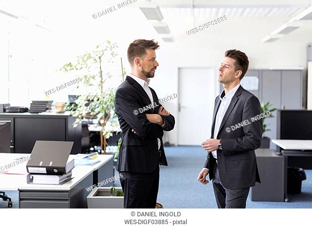 Two businessmen standing in office, discussing solutions
