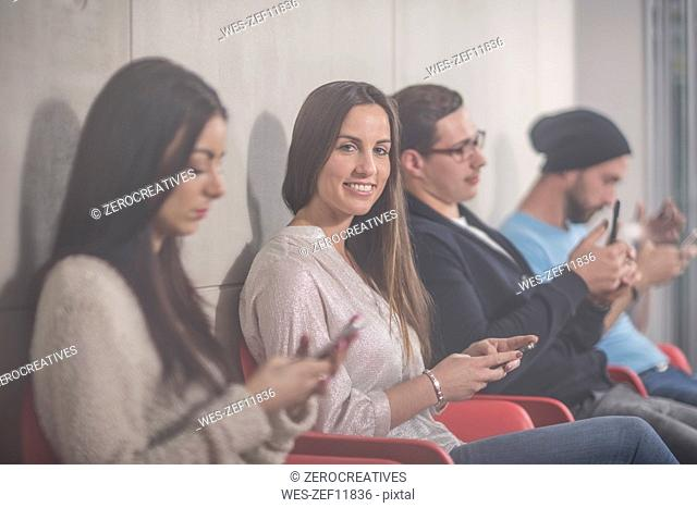 Portrait of smiling businesswoman waiting with colleagues