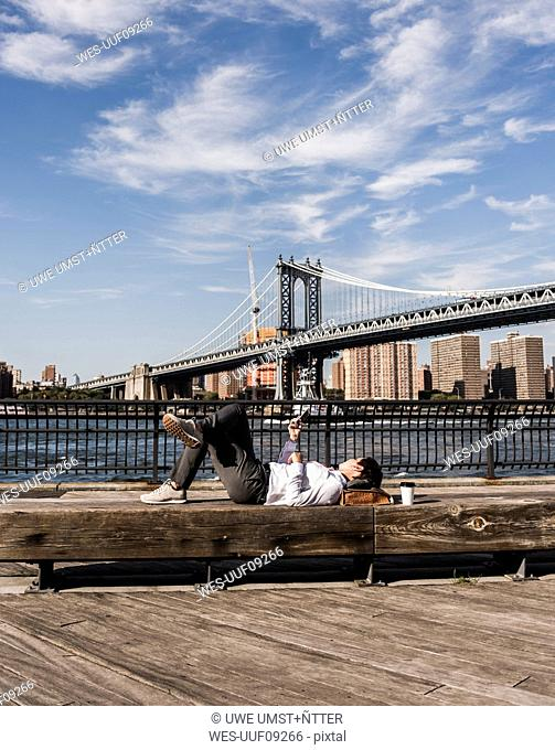 USA, Brooklyn, businesswoman lying on bench listening music with earphones