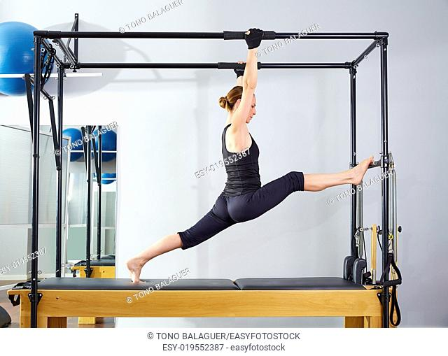 Pilates woman in cadillac legs split reformer exercise at gym