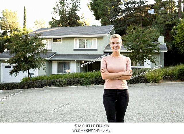 Portrait of smiling woman in front of her home