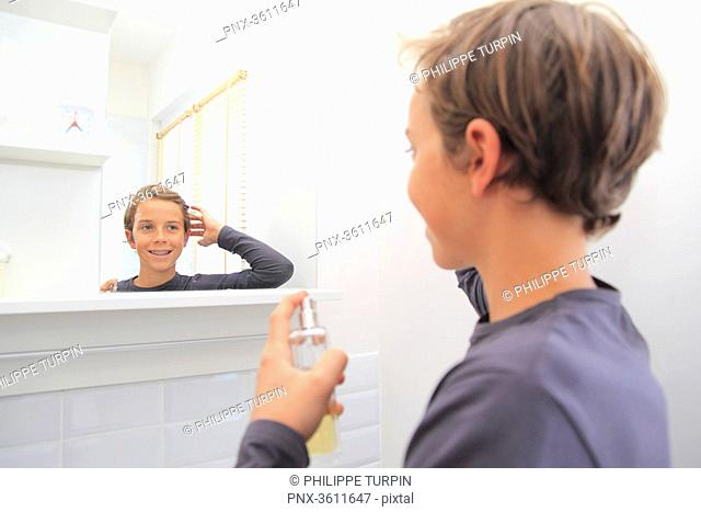 France, teenager in his bathroom using parfum