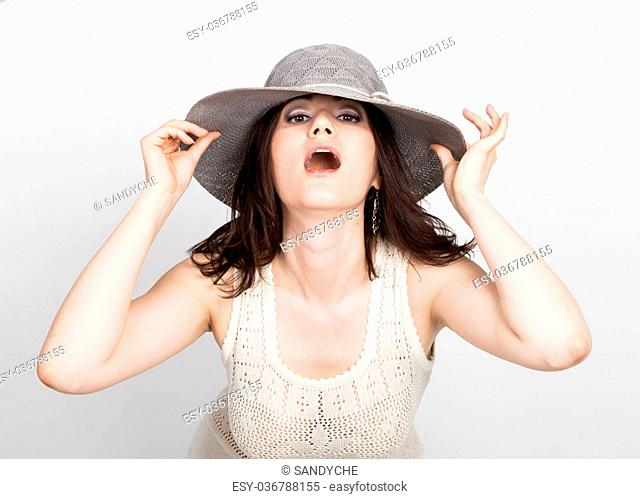 beautiful young brunette woman holding a broad-brimmed hat. girl flirting concept. expression of different emotions