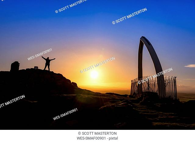 Great Britain, Scotland, East Lothian, North Berwick, North Berwick Law, whale jaw bone arch, sunset, female tourist with raised arms