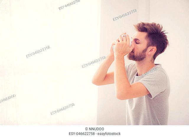 american man with cup of coffee in bedroom with morning