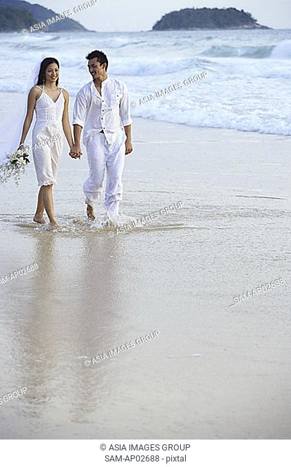 Bride and groom walking on beach, holding hands