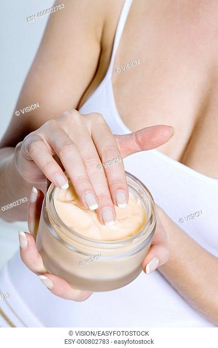 close up woman on studio isolated background applying mosturiser cream lotion bodycare