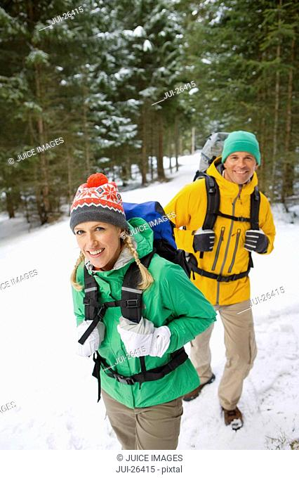 Portrait of happy couple backpacking in snowy woods